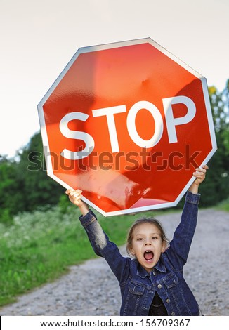 "Beautiful little girl screaming and holding red sign ""STOP"". - stock photo"