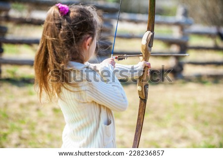 Beautiful little girl shoots bow at entertainment park. - stock photo