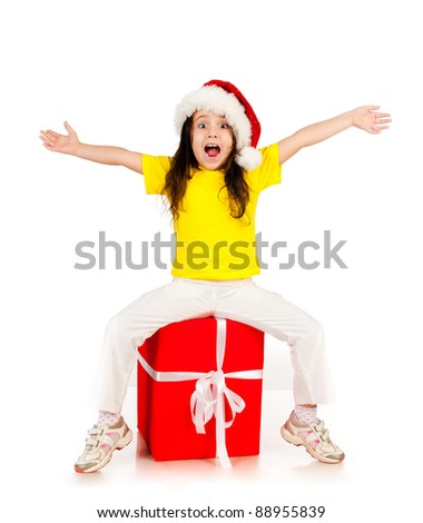 beautiful little girl sitting on red gift in santa hat - stock photo
