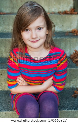 Beautiful little girl sitting on steps outdoors, wearing colorful dress - stock photo