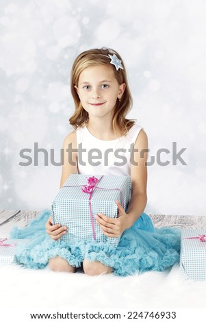 Beautiful little girl sitting with christmas presents - stock photo