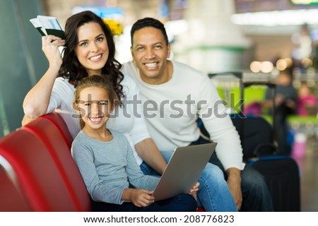 beautiful little girl sitting with her parents at airport - stock photo