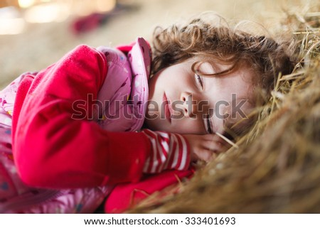 Beautiful little girl sleeping peacefully in hay with hands under her head. - stock photo