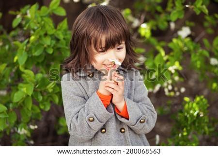 Beautiful little girl smelling spring flower - stock photo