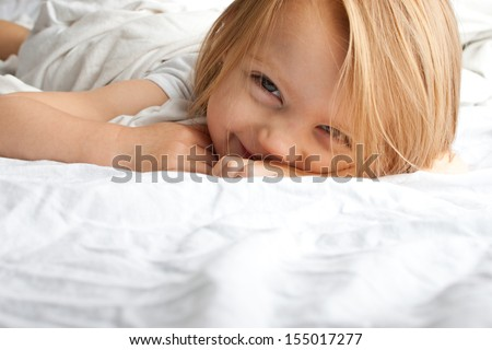 Beautiful little girl smiling after waking up - stock photo