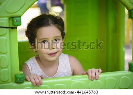 Beautiful little girl smiling in toy house window on playground. Happy child, adorable little girl, having fun outdoors hiding in plastic playhouse in playground on a sunny summer day - stock photo