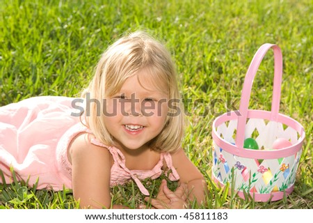 Beautiful little girl smiling with Easter eggs and basket - stock photo