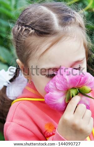 Beautiful Little Girl Sniffs a Flower in a Garden - stock photo