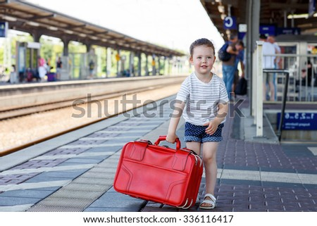 Beautiful little girl walking with big red suitcase on a railway station. Kid waiting for train and happy about a journey. People, travel, lifestyle concept - stock photo