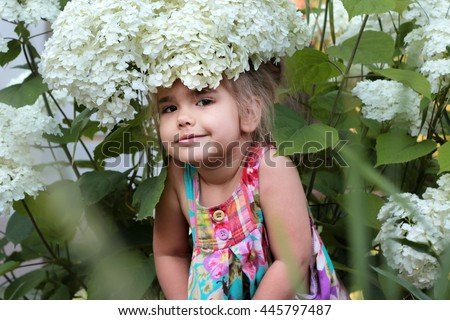 Beautiful little girl wearing a big white flower on the bush like a hat, outdoor portrait, summer beauty - stock photo