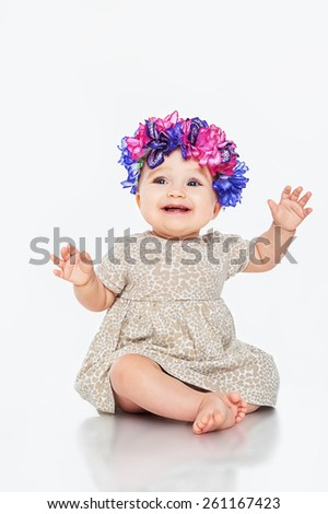 Beautiful little girl wearing a wreath, on a gray background - stock photo