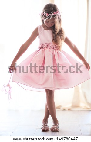 Beautiful little girl wearing fairy costume with magic wand - stock photo