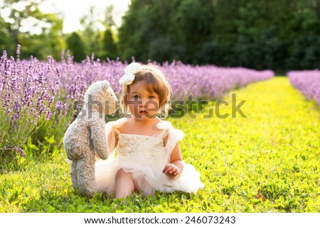 Beautiful little girl wearing white dress sitting in lavender field playing with teddy bear - stock photo