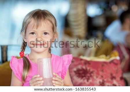 Beautiful little girl with a glass of chocolate milk  - stock photo