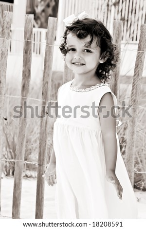 Beautiful little girl with a pretty smile and curly brunette hair. - stock photo