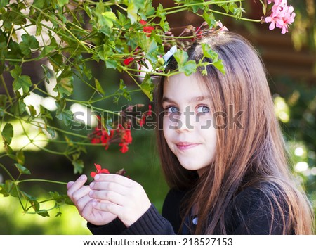 Beautiful little Girl  with a red  flowers - stock photo
