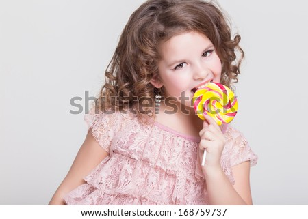 Beautiful little girl with big candy lollipop isolated in studio. Lovely child with sweet candy lollipop on white background. Happy girl eat sugar candy. - stock photo