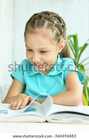 Beautiful little girl with book - stock photo