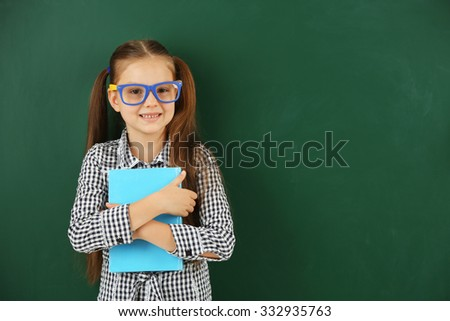 Beautiful little girl with book,  on blackboard background - stock photo