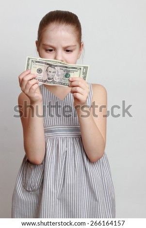 Beautiful little girl with cash money dollars US - stock photo