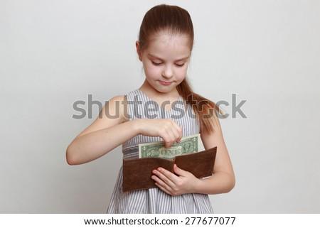 Beautiful little girl with cash money dollars US - stock photo