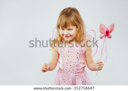 Beautiful little girl, with curly blond hair, wearing on pink dress and fairy wings, posing with magic street, on white background, in studio, waist up - stock photo