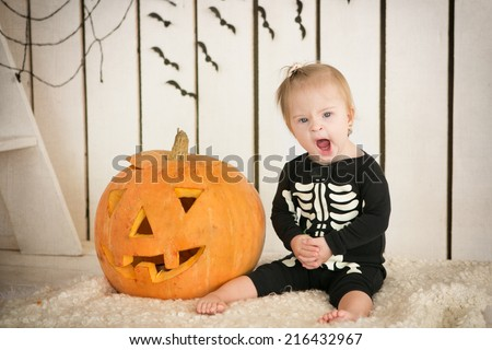 beautiful little girl with Down syndrome sitting near a pumpkin on Halloween dressed as a skeleton - stock photo