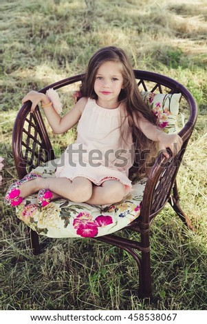 beautiful little girl with flowing hair sitting in a wicker chair. a girl wearing a pink dress. in the background is the field - stock photo