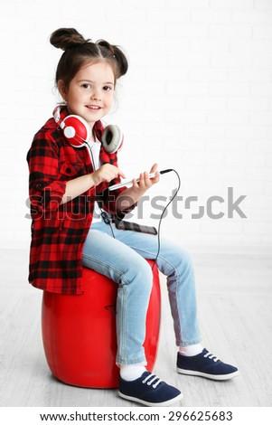 Beautiful little girl with headphones in room - stock photo