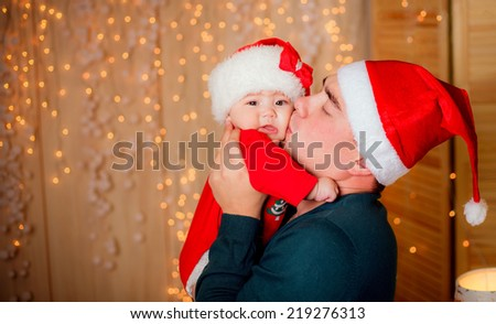 beautiful little girl with her ??father at the hands near the Christmas tree at home. new year. Christmas decoration, illumination - stock photo