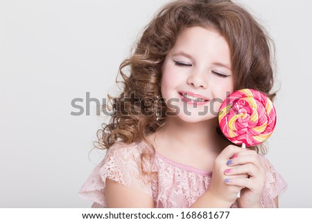 Beautiful little girl with lollipop candy. isolatad in studio. Lovely child with sweet candy lollipop on white background. Happy girl eat sugar candy.  - stock photo