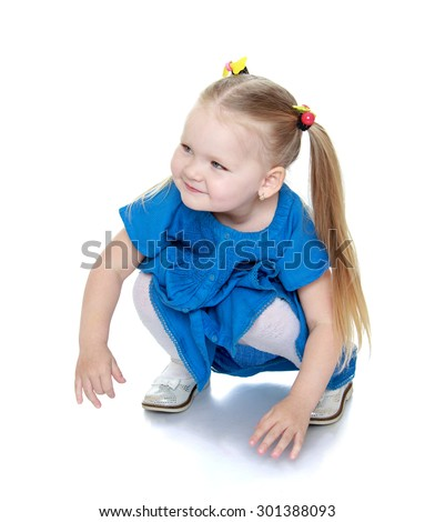 Beautiful little girl with long blonde bunches that adhere colorful erasers. Girl squatting in a blue long dress-Isolated on white background - stock photo