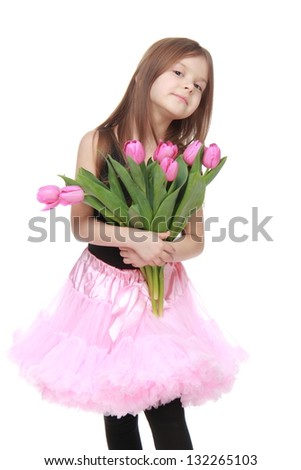 Beautiful little girl with long hair in a pink tutu holding a bouquet of pink tulips on white background - stock photo