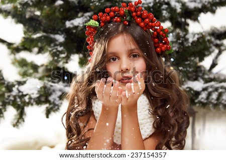 Beautiful little girl with long hair in winter white sweater with a wreath of red berries on a head sits in the snow under the Christmas tree gift for New Year Merry Christmas card - stock photo