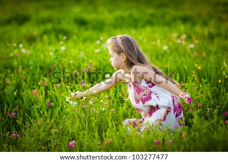 Beautiful little girl with long hair playing on the meadow flowers - stock photo