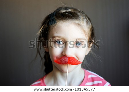 Beautiful little girl with mustache-shaped lollipop - stock photo