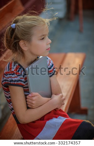 Beautiful little girl with on Tablet PC, sitting on bench. - stock photo