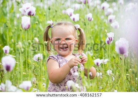 Beautiful little girl with pair of glasses on a meadow - stock photo