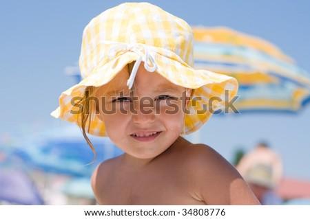 Beautiful little girl with sun hat on beach - stock photo