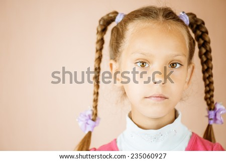 Beautiful little girl with tails close up on light brown background. - stock photo