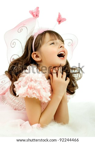beautiful  little girl with wings, sit and  smile on white background, isolated - stock photo