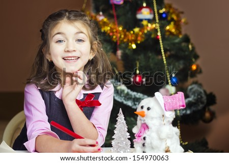 Beautiful little girl writes letter to Santa Claus in festively decorated room - stock photo