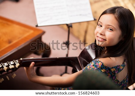 Beautiful little Hispanic girl playing the guitar at home - stock photo