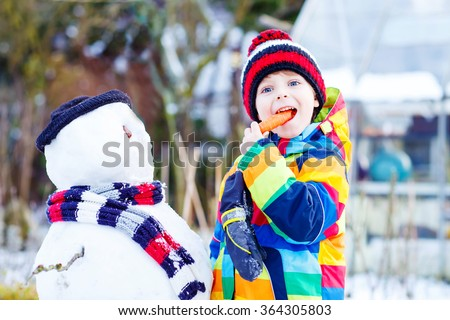 Beautiful little kid boy making a snowman and eating carrot. child playing and having fun with snow on cold day. Active outdoors leisure with kids in winter. - stock photo