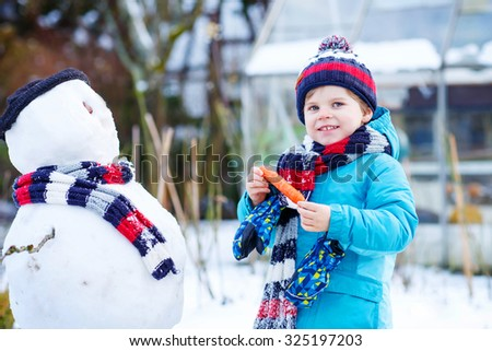 Beautiful little kid boy making a snowman and eating carrot, playing and having fun with snow, outdoors  on cold day. Active outdoors leisure with children in winter. - stock photo