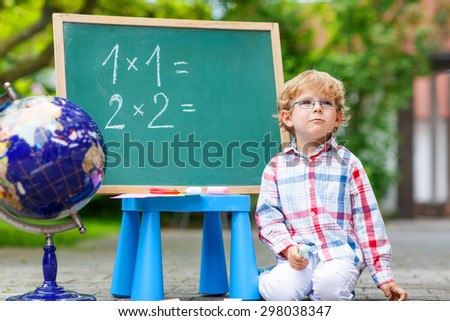 Beautiful little kid boy with glasses at blackboard thinking about mathematics, outdoor. school or nursery. Back to school concept - stock photo