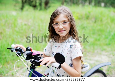 Beautiful little  kid girl  in glasses riding a bicycle outdoor - stock photo