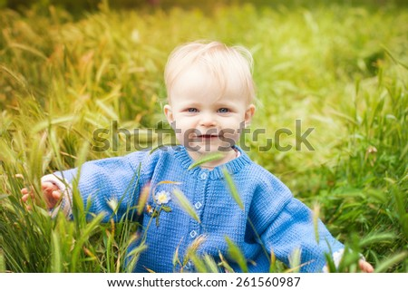 beautiful little kid walks on the field. Smiling girl in a blue blouse spring meadow. Nature walks. Picnic. Outdoors. Cute little child on the meadow in spring day - stock photo