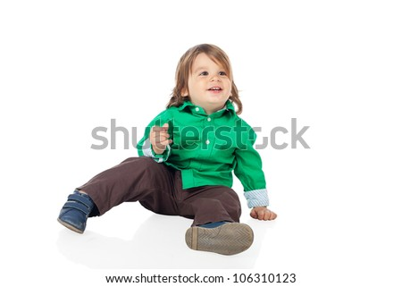 Beautiful little kid, 2 years old boy, sitting on the floor and looking away, wearing shirt and jeans. High resolution image isolated on white background with copy space. Studio shot. - stock photo