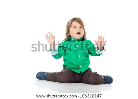 Beautiful little kid, 2 years old boy, sitting on the floor with hands up, wearing shirt and jeans. High resolution image isolated on white background with copy space. Studio shot. - stock photo